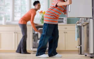 Boy Looking in Refrigerator While Mother Unloads Dishwasher