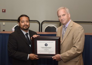 Richard Medina (left), U assistant professor of geography, accepting the Center of Academic Excellence in Geospatial Sciences certificate from Richard Cardillo (right), director of the Pentagon's National Geospatial-Intelligence Agency.
