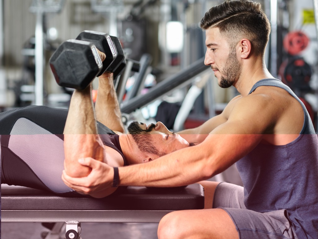 Personal fitness trainer helping a man at a chest workout with heavy dumbbells