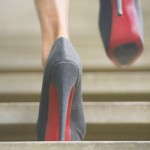 Upward view of woman in high heel stiletto shoes walking up wooden stairs with blurred background.