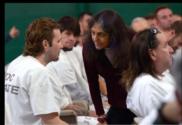 Biology professor Nalini Nadkarni speaks with an inmate.
