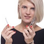 Close up Young Blond Woman in Black Clothing Holding a Tobacco and E-Cigarette on a White Background.