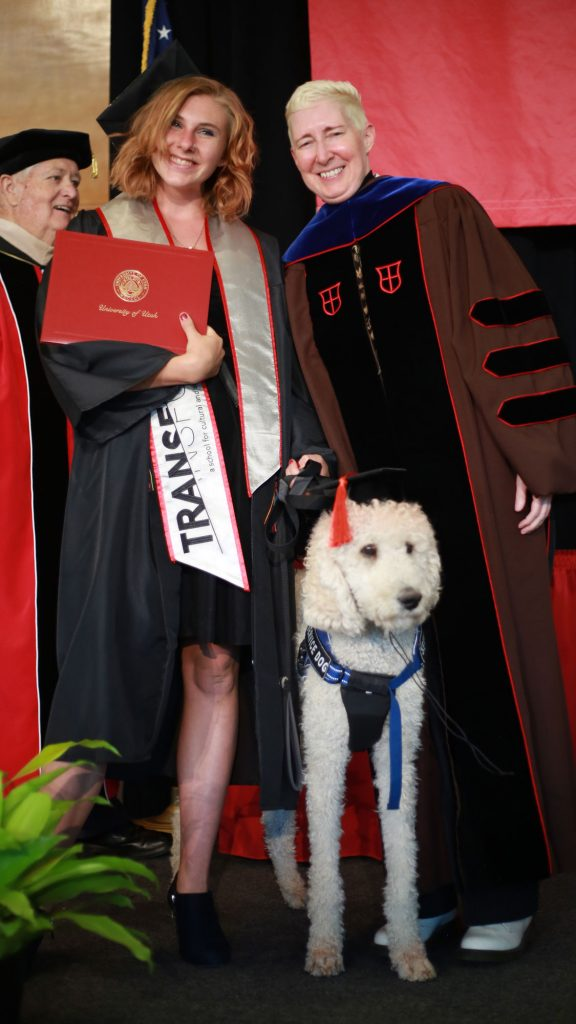 Sierra Bruggink graduating with a major in gender studies and a minor in disability studies, her service dog, Gus, and Kathryn Bond Stockton, Dean of Transform.