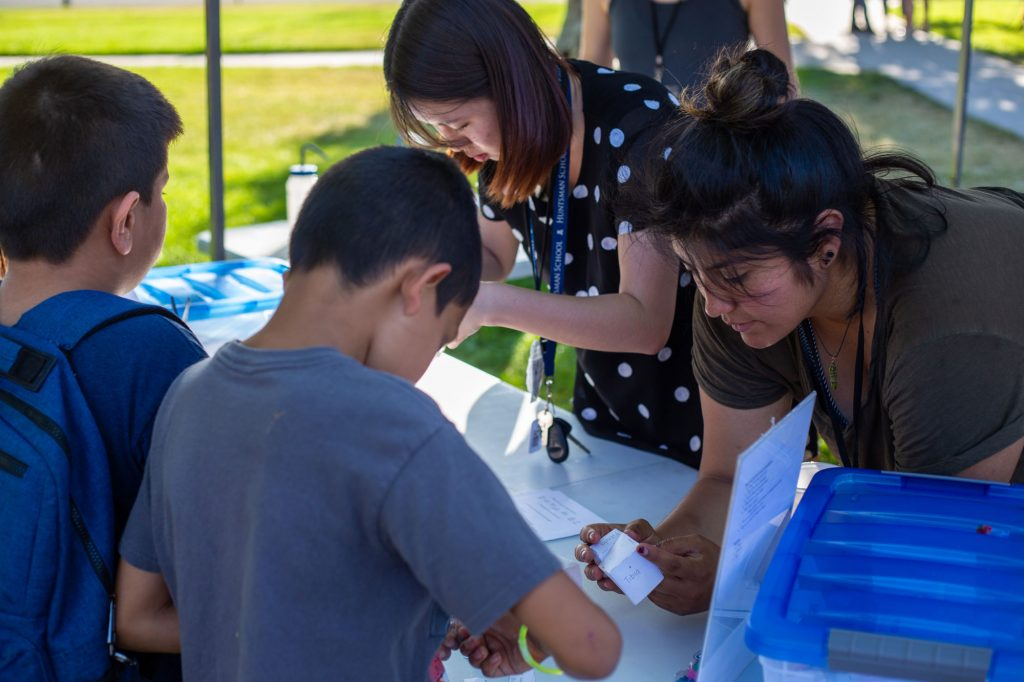 Anahy Selcedo (right) and another volunteer guide participants through an activity to build a paper knee in Science in the Park. Selcedo spearheaded the program at the U, which goes to parks in the West Valley.