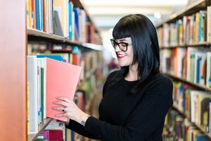 Librarian Adriana Parker takes book off shelf