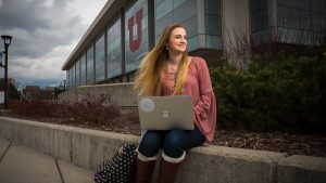 Student sits with laptop outside Marriott Library