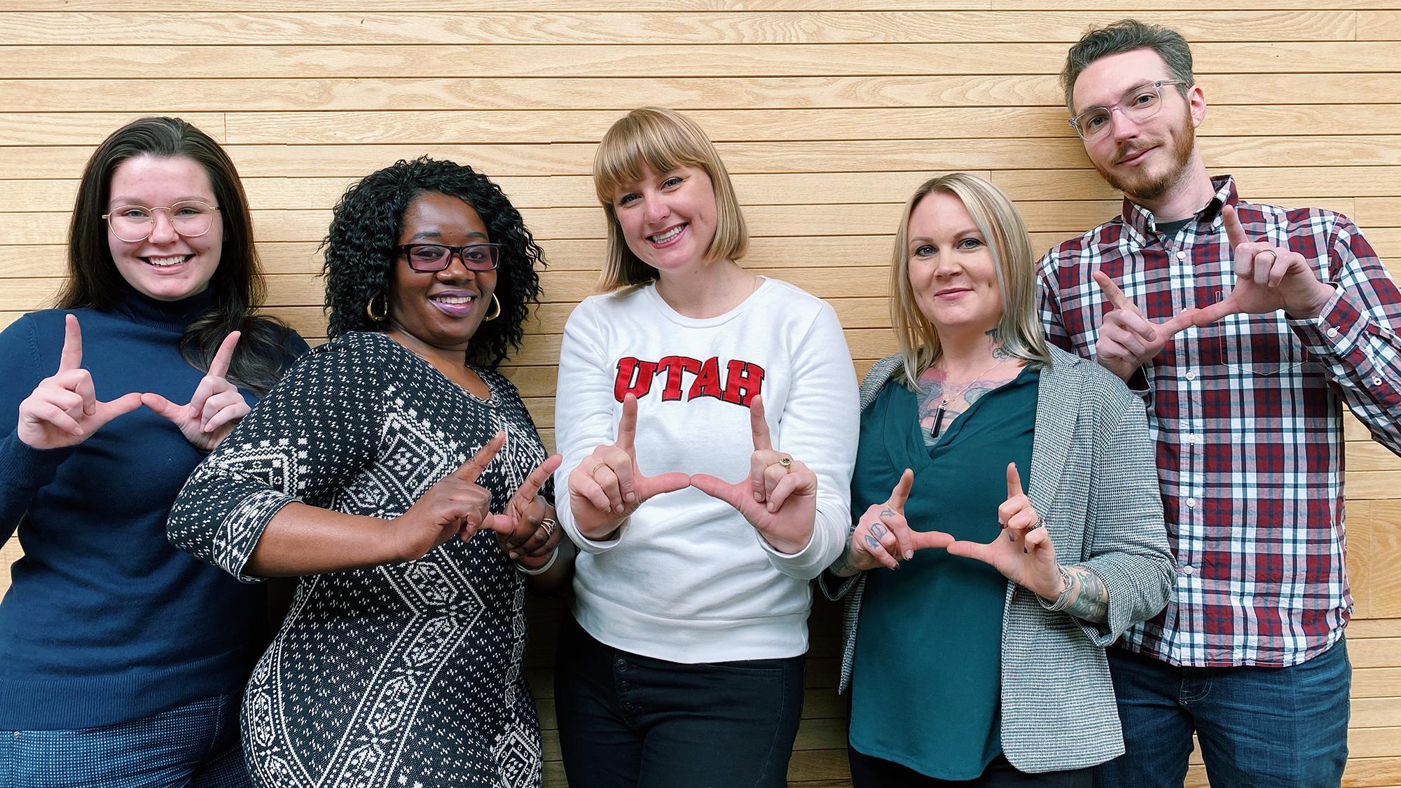 Five members of the victim-survivor advocacy team flash the U