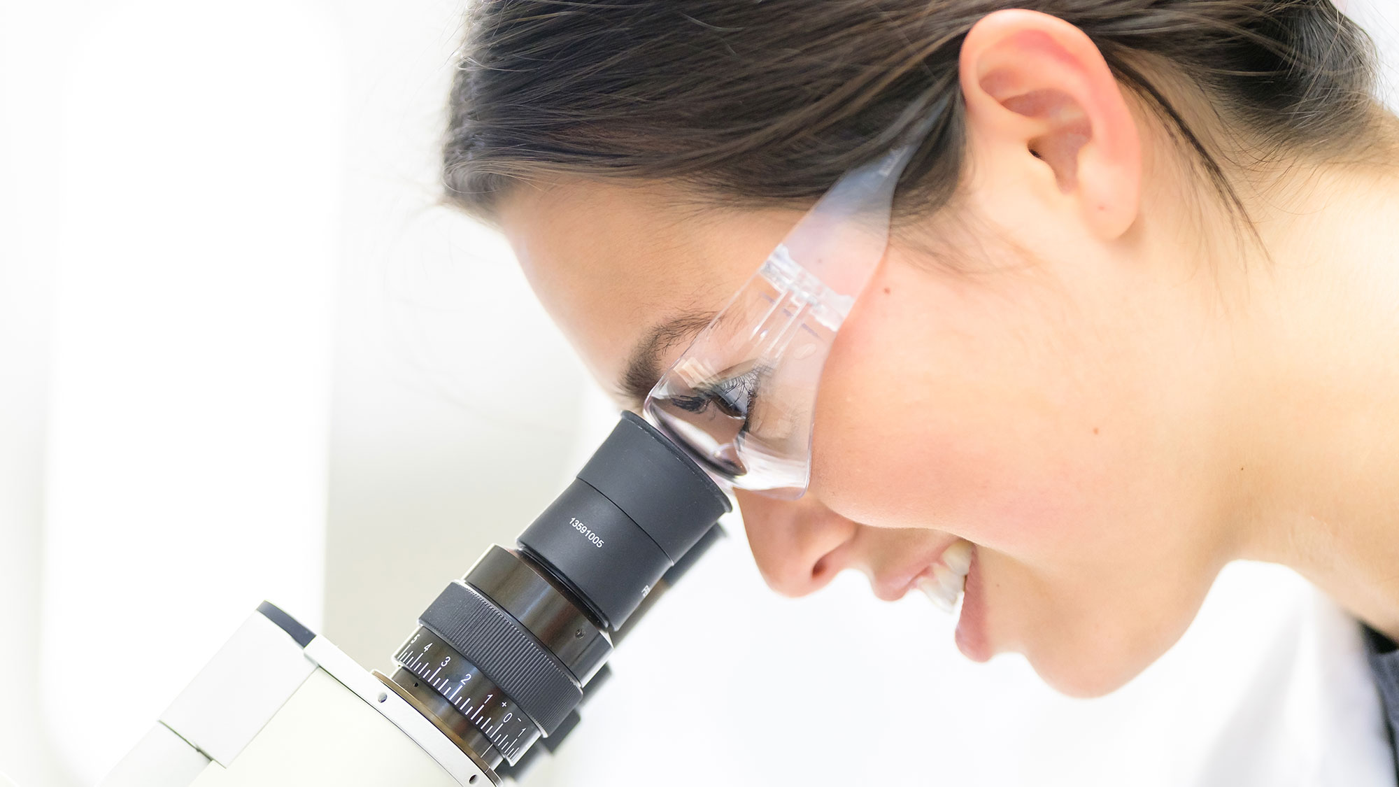 A woman scientist looks through a microscope