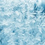 Feathery ice crystals on a blue surface