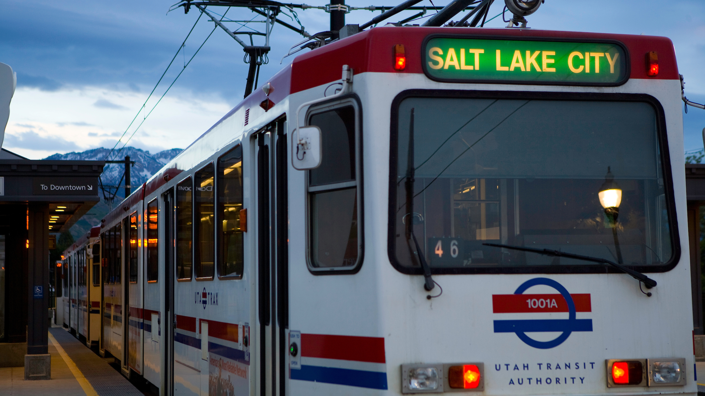 A light rail TRAX train departing a station, with a sign indicating the train is headed to Salt Lake City