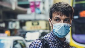 A man on an urban street wearing a surgical facemask