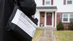 A 2020 Census worker with an official satchel approached a residence.