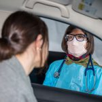 A woman doctor wearing a face mask looks through the window at a woman who may have COVID-19 at a drive-up testing site.