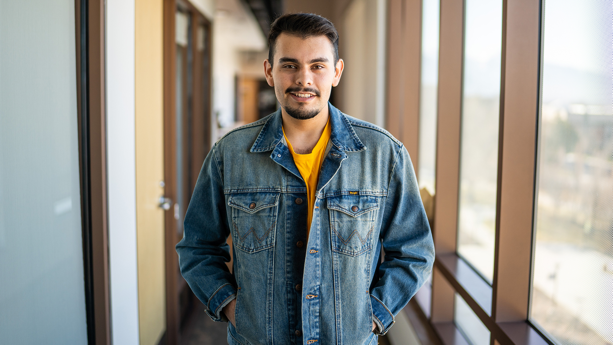 Latino male student wearing jean jacket poses for photo