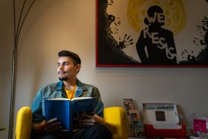 "Latino student Johnny Rodriguez poses for photo while reading a book. Background art reads, ""We resist."""