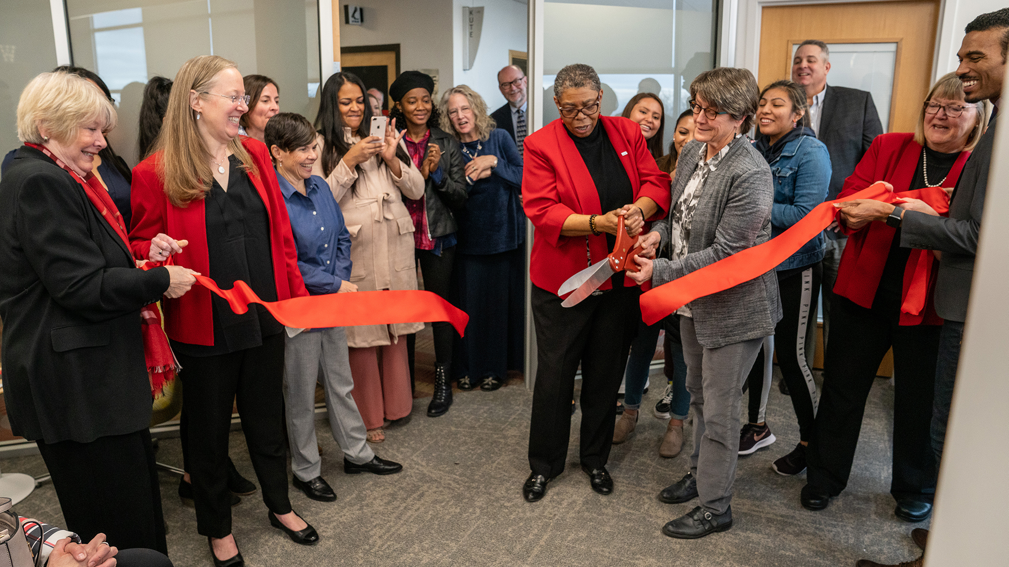 Group gathered cutting ribbon to new Women's Resource Center