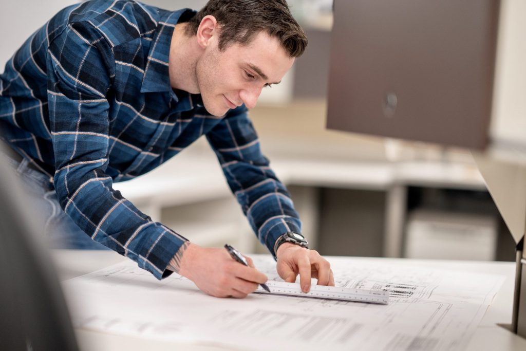 Man wearing wearing blue plaid shirt working at a drafting table.