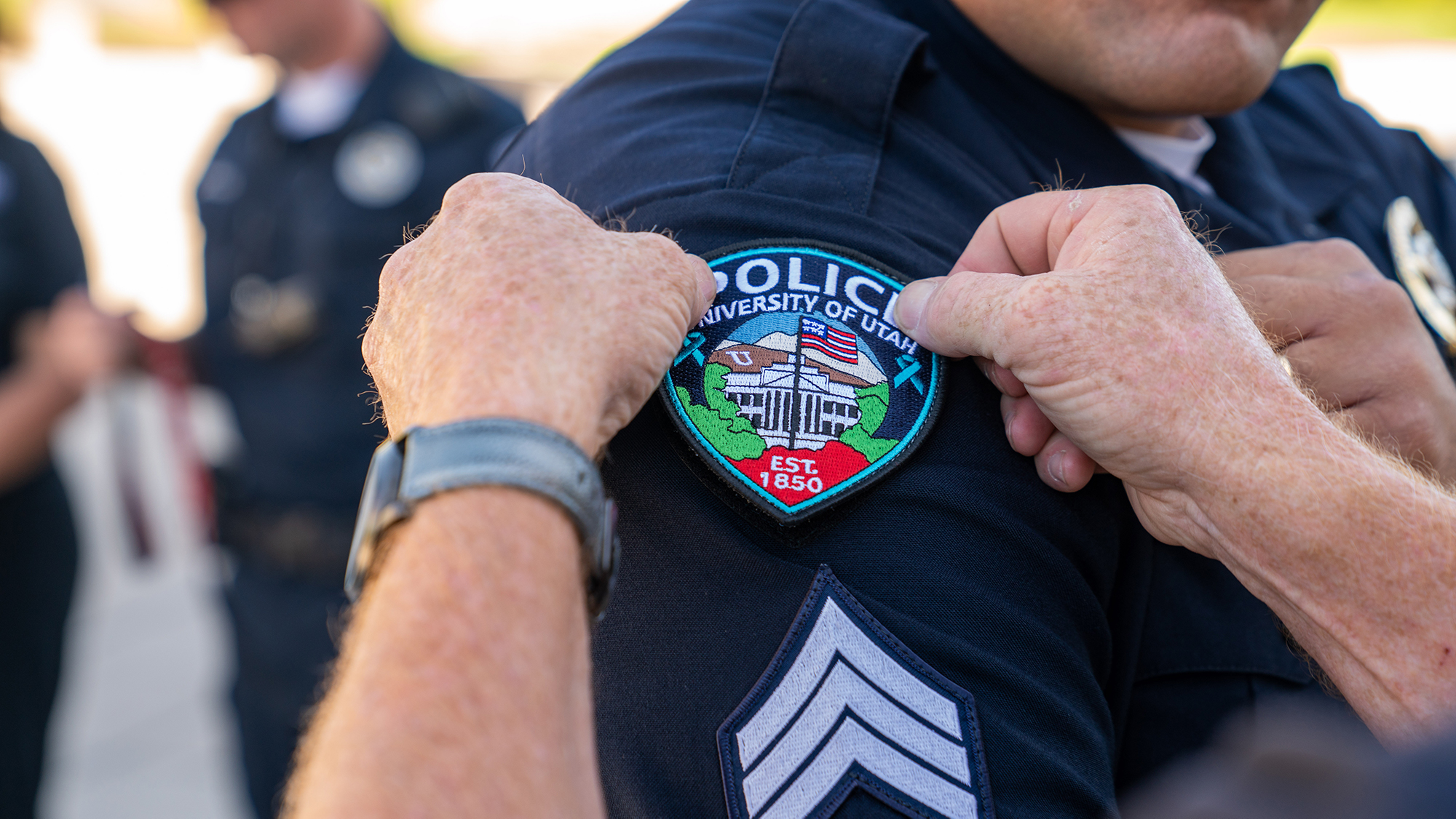 Sexual Assault Awareness Month patch being placed on University Police Officer's uniform