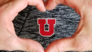 "hand heart over a small block ""U"""