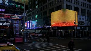ZAZ Corner, a digital gallery that showcases artwork on a huge LED screen in Times Square, displays a video of gold coins dissolving in a solution.