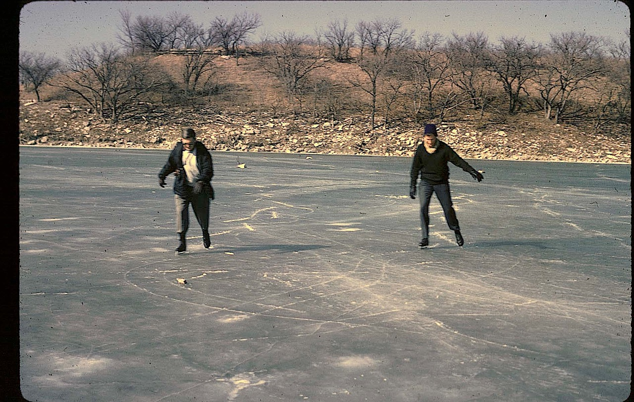 Old photo of two men ice skating on a lake.