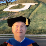 screenshot of a Dean giving virtual congratulations to grads with virtual block U in background.