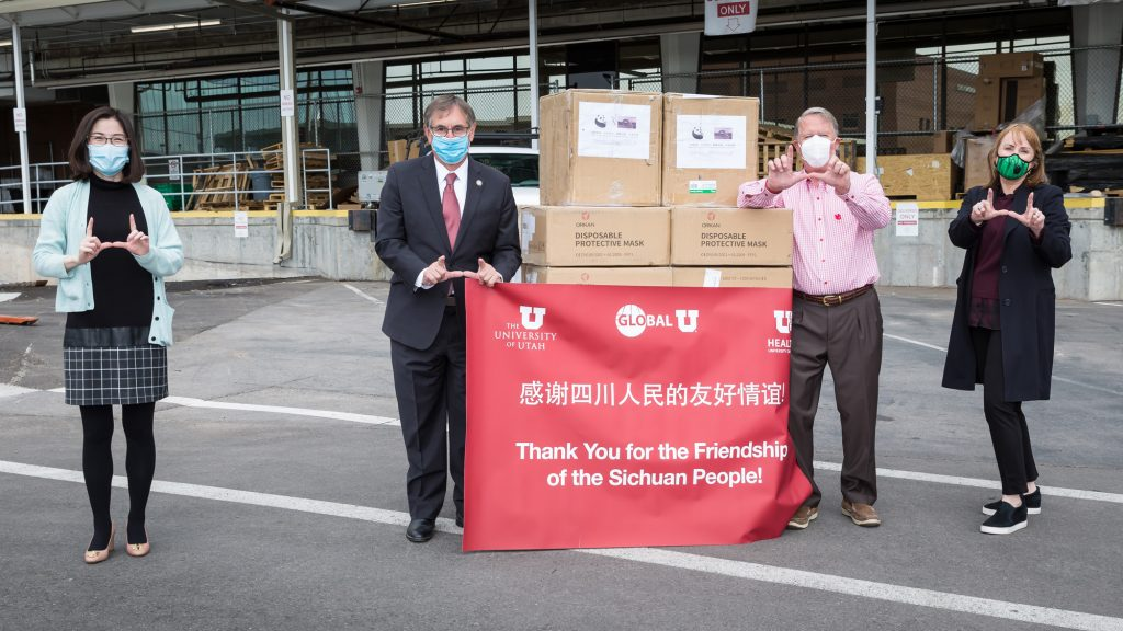 Four people flashing the U next to a delivery of PPE masks.