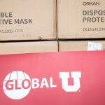 """Boxes of """"Disposable Protective Masks"""" with a Global U banner below."""