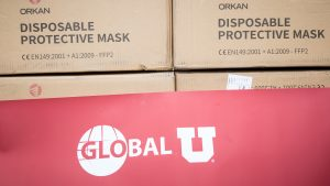 "Boxes of ""Disposable Protective Masks"" with a Global U banner below."