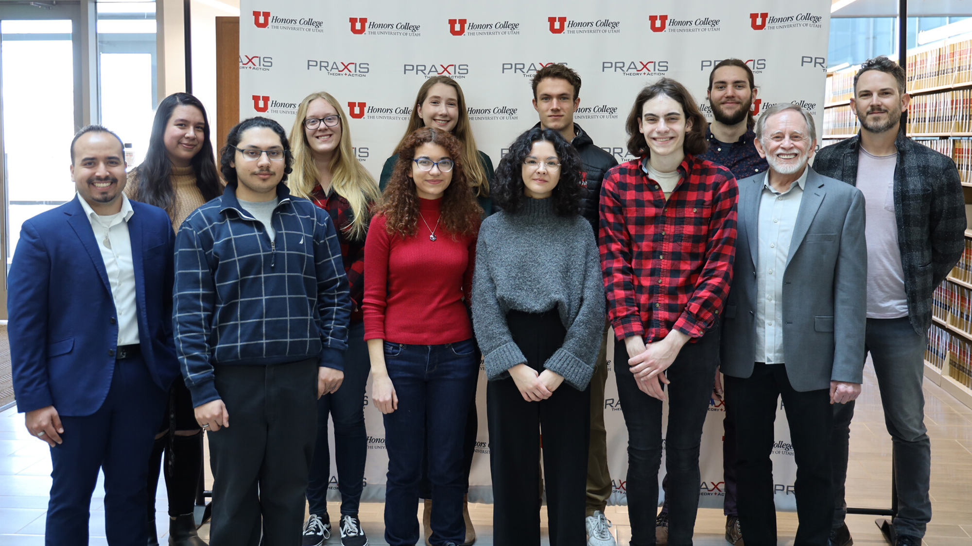"group of 10 students and 2 instructors standing in front of background that reads, ""University of Utah Honors College"" and ""Praxis Theory + Action"""
