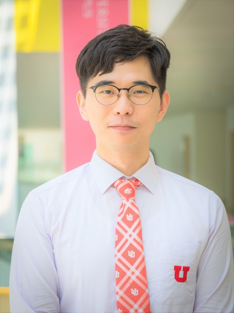 Asian man in white shirt, red plaid tie and glasses.