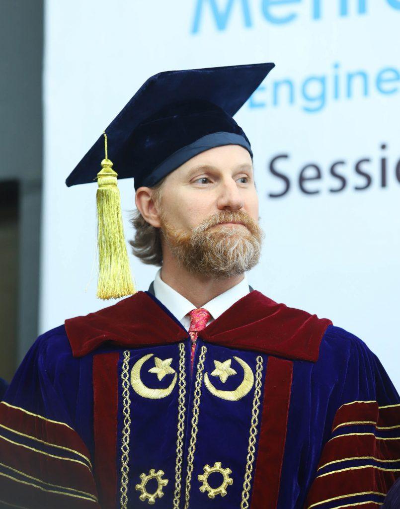 Bearded caucasian man in graduation regalia