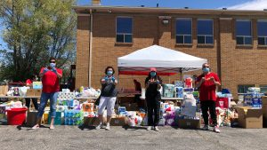 "Photo of four people wearing masks, standing several feet apart with fingers held up in ""u"" shape in front of piles of donated supplies such as water and toilet paper."