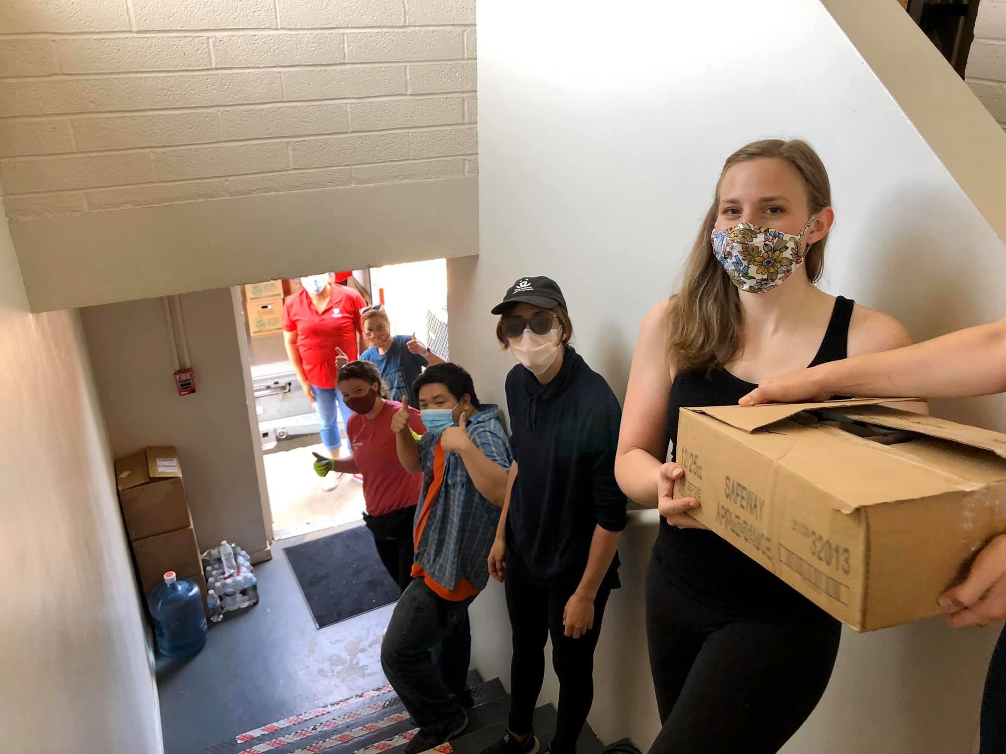 people wearing masks form a line up a flight of stairs as they pass items for delivery up.