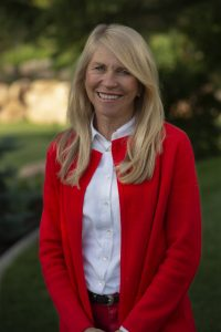White woman with long blonde hair wearing a red cardigan over a white button up shirt outside.