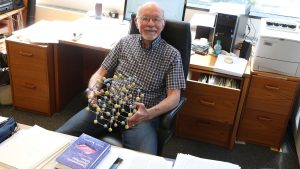 Gerald Stringfellow, an older man with white hair, and white goatee and wire-rimmed glasses, sits at his desk, holding a model of some kind of molecule — sticks attached to yellow and white balls arranged to form a three-dimensional grid thing.