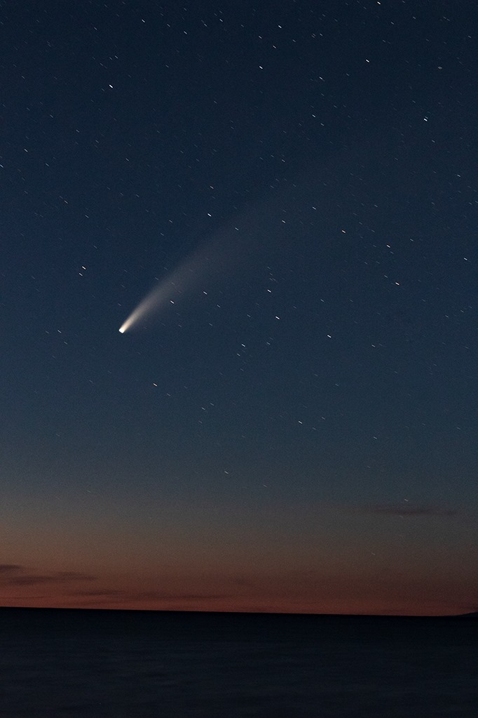 The comet shoots across a late dusk sky with colors fading from dark on the top to light near the horizon.