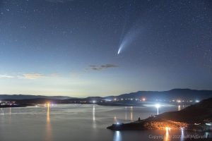 The comet falls across the sky over a reservoir with lights all around the outside of it.