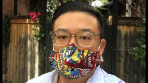 Clement Chow, an asian American man, wears a colorful mask in a selfie photo.