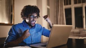 Man celebrates while looking at laptop.