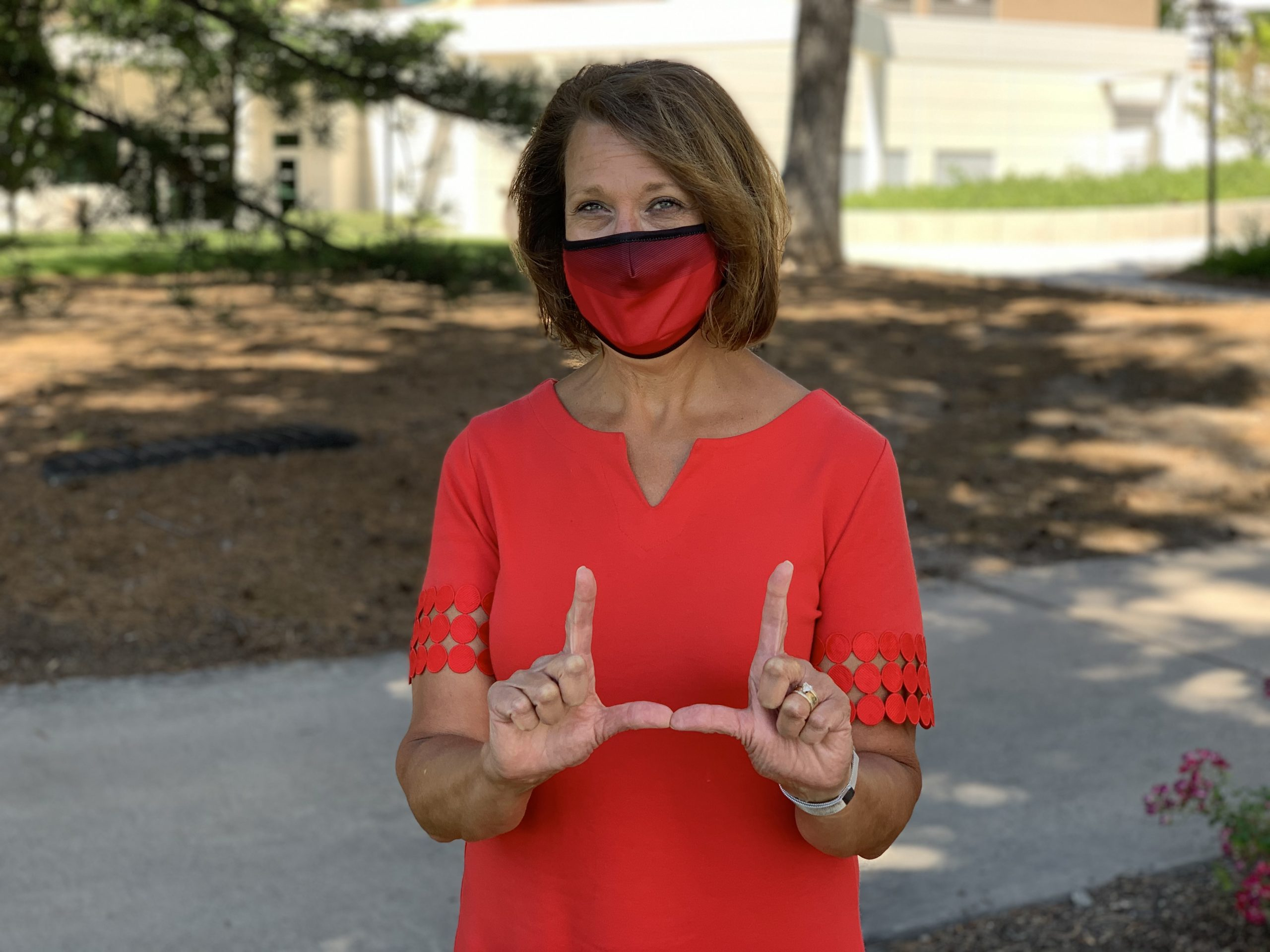"University of Utah president Ruth Watkins ""flashing the U"" while wearing face covering."