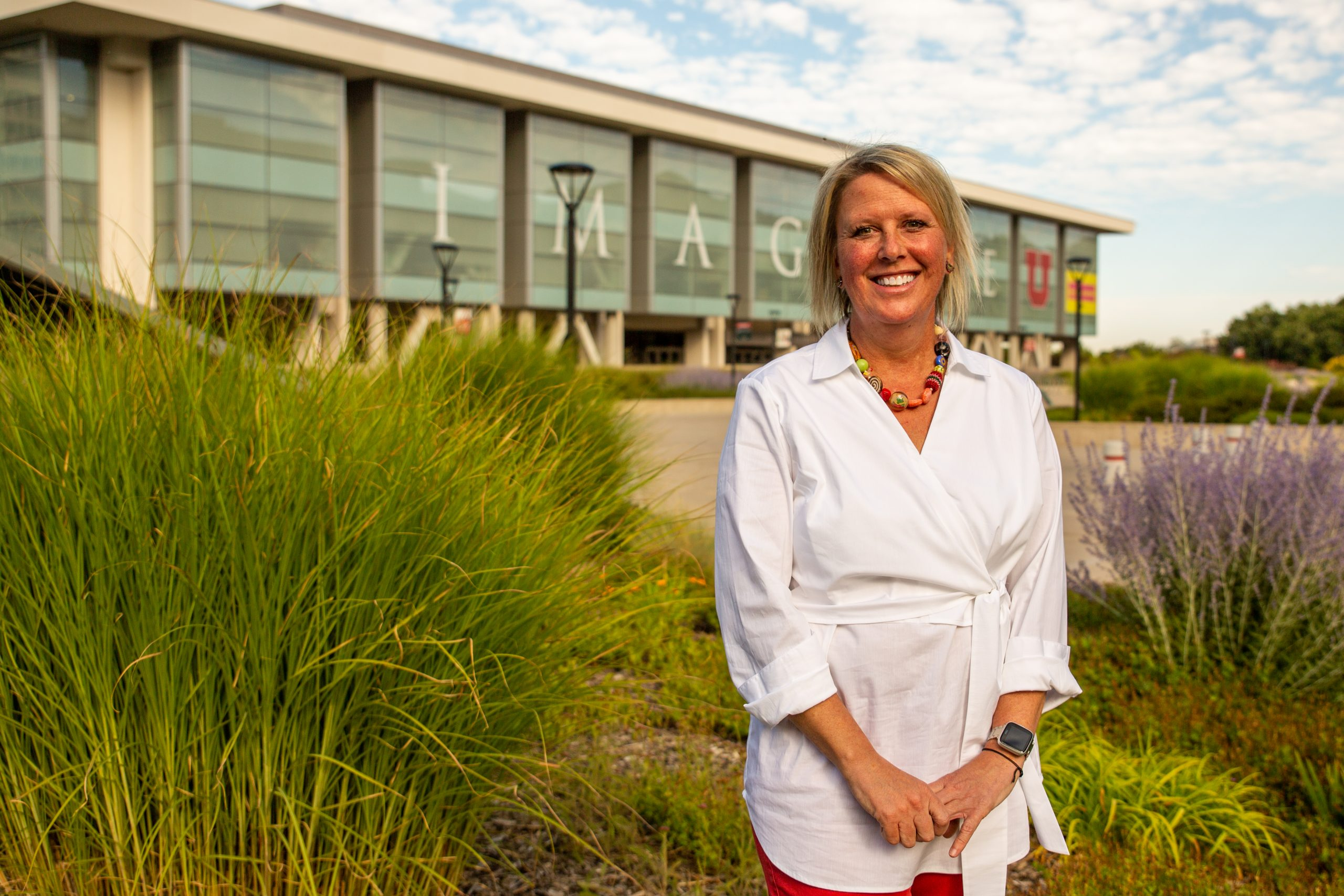 Karen Paisley, 2020 New Student Welcome faculty speaker smiles for photo outside Marriott Library at the University of Utah