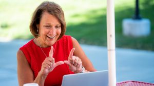 University of Utah president Ruth Watkins flashes the U to her laptop computer screen while zooming with students.