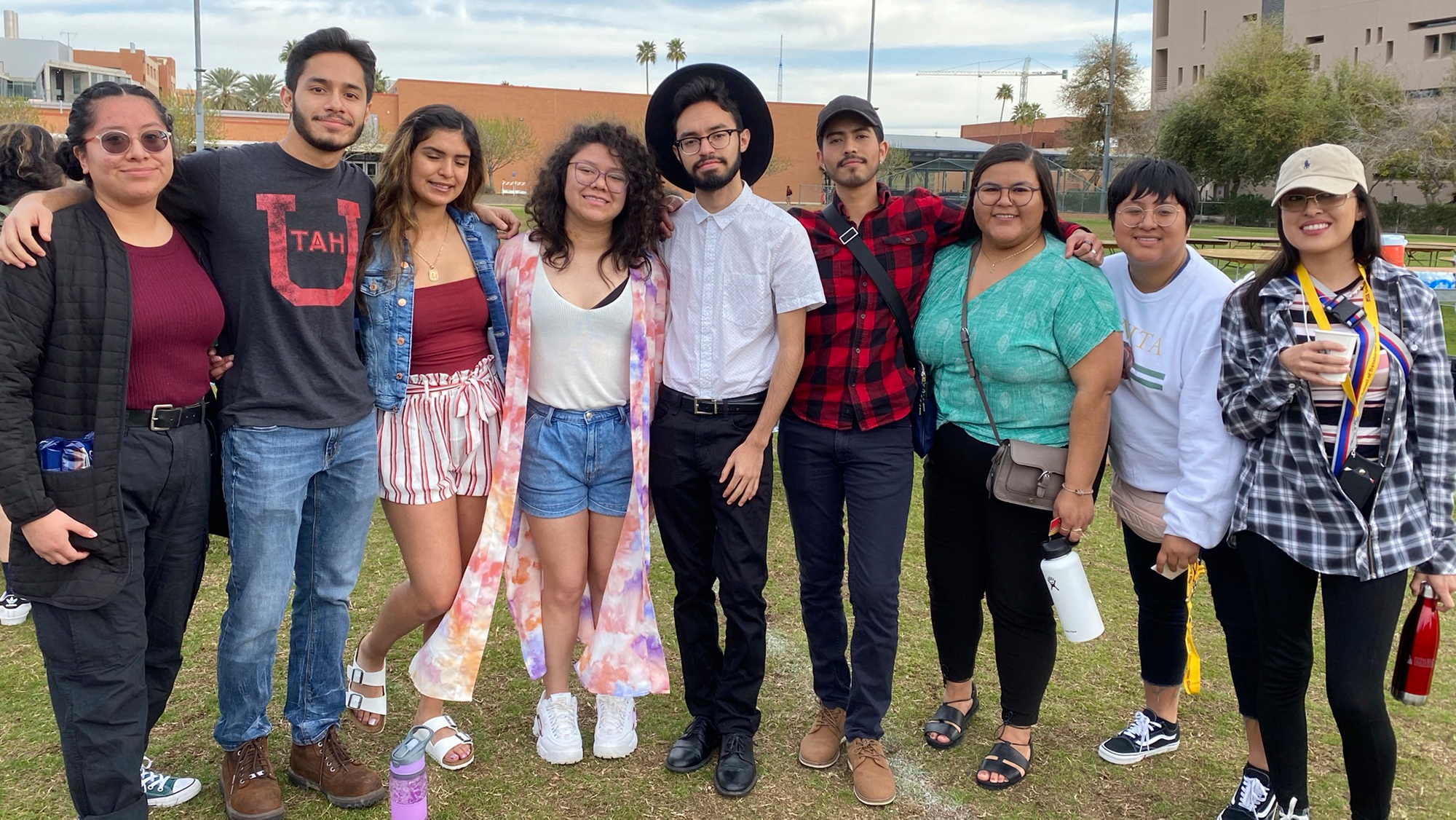 nine students standing with their arms around one another in straight line for photo