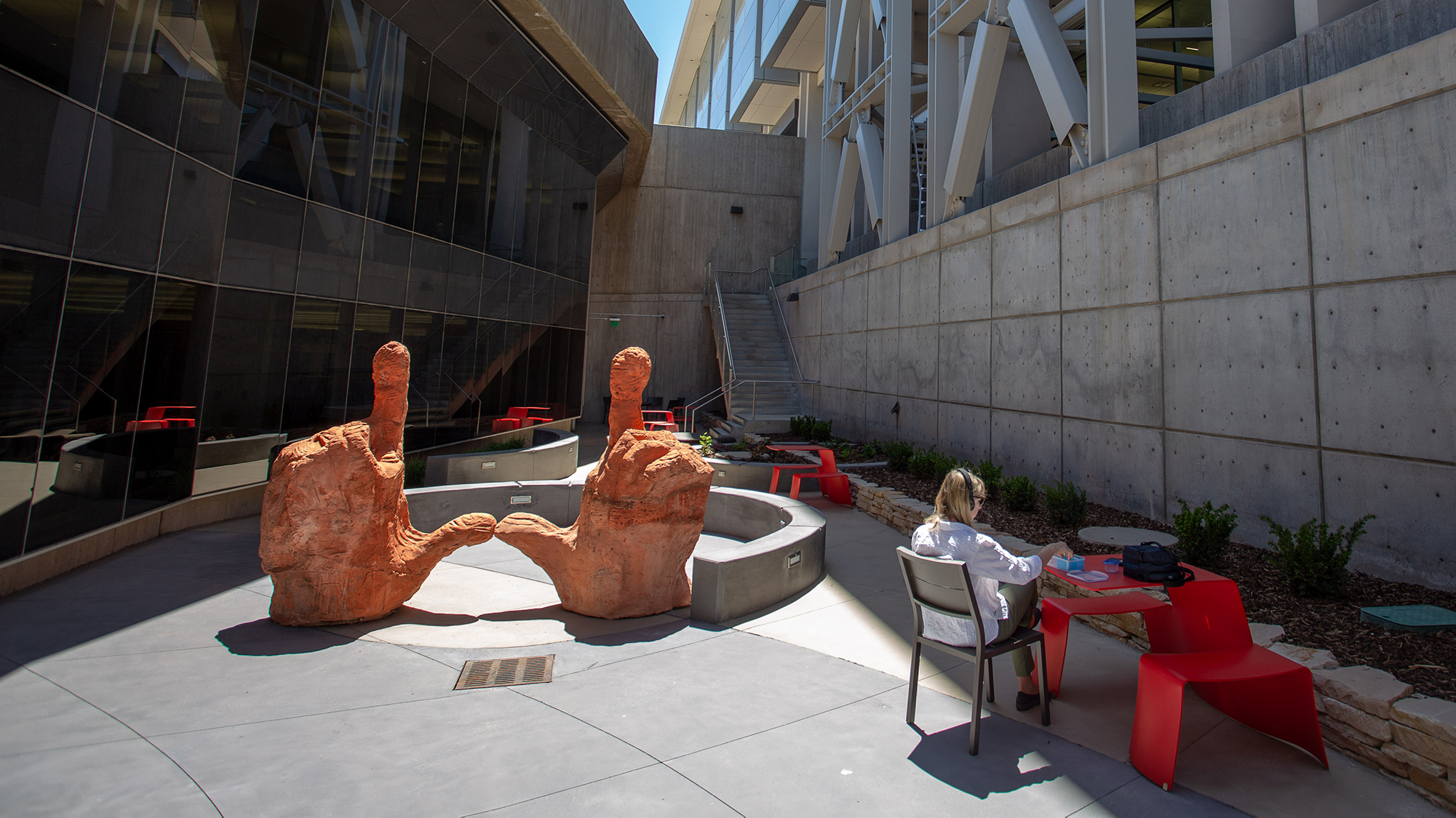 "student sitting at table studying with headphones on, next to large sculpture of two hands with thumbs and pointer fingers in the shape of a ""U."""