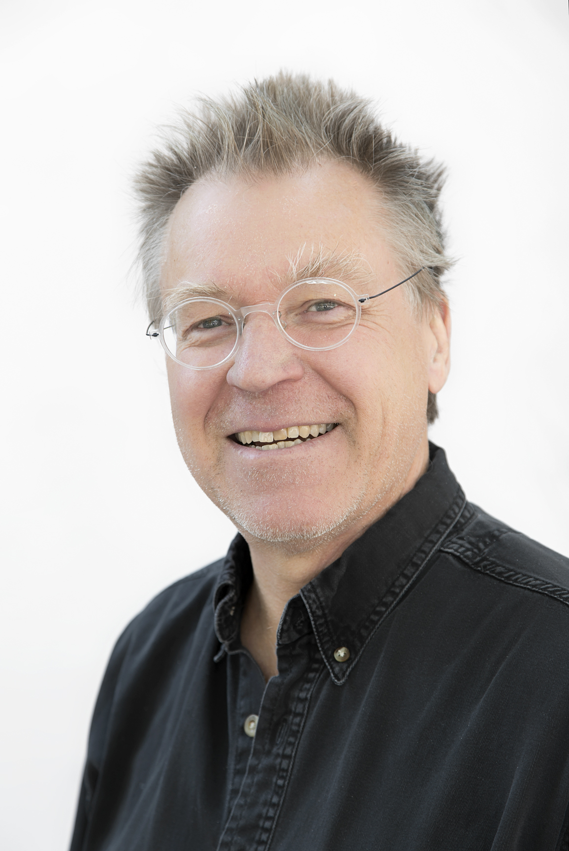 A headshot of Erik Jorgenson, with round rimless glasses and gray hair.