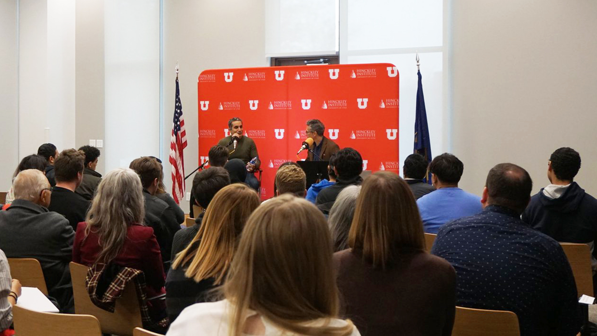 sitting audience members face a stage with two people sitting and talking with a University of Utah backdrop behind them.