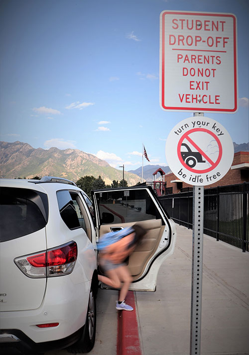 A kid jumps out of a car at a school drop off zone. A sign that reminds parents to turn their cars off idle is in the foreground.