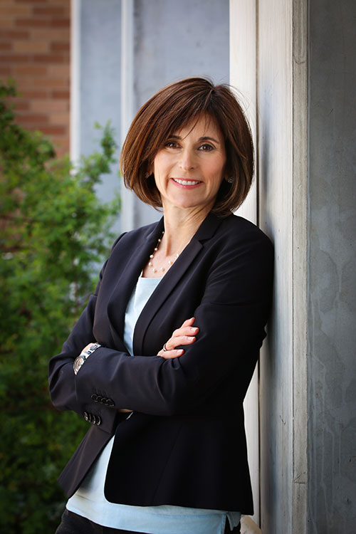 Kerry Kelly leans against a wall for a headshot. She is a white scientist with short brown hair wearing a black blazer.