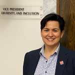 """Mary Ann Villarreal poses for photo in front of sign reading, """"vice president, Equity, Diversity, and Inclusion"""""""